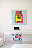 Poster above simple white desk and colourful chair