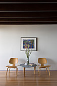 Coffee table and classic chairs below picture on white wall