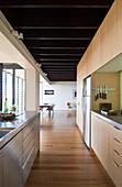 Moderne, offene Küche mit Holz- und mit Edelstahlfronten