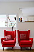 Two red armchairs with scatter cushions in front of white wall