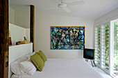 Double bed, TV and modern artwork on wall in bedroom