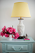 Table lamp with ceramic base and deep pink flowers on bedside table