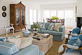 Blue sofas and chairs around coffee table and antique display case in living room