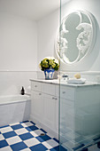 Washstand below round mirror in bathroom with blue-and-white floor tiles