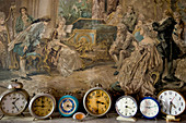 Collection of alarm clocks in front of painting