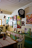 Bench, green sideboard, station clock and gallery of pictures in shabby-chic interior