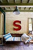 Antique bench below large red letter S on brick wall on roofed terrace