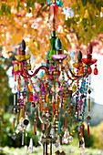 Chandelier with brightly coloured beads in garden