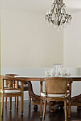 Antique dining table and chairs below chandelier in dining room