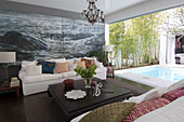 Coffee table and sofas with scatter cushions in front of maritime mural wallpaper; view of pool on terrace
