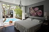 Floral artwork above double bed with view of pool