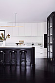 Open kitchen with white cabinets, kitchen island and dark wooden floor