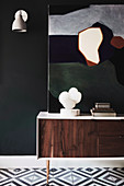 Sideboard with sculpture and modern art next to wall lamp