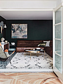Coffee table and leather couch in the living room with dark green wall