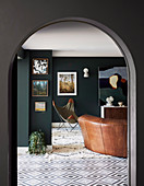 View through arch into living room with dark green wall