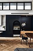 Hoher, offener Wohnraum mit schwarzen Einbauten und Rundbogen-Ausschnitt