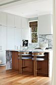 White, floor-to-ceiling fixtures and breakfast bar in open kitchen