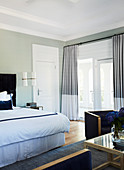 Spacious, elegant bedroom with light green walls
