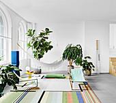 Liegestühle auf buntem Teppich, Zimmerpflanzen und Hängematte im Wohnzimmer