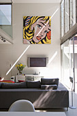 Pop Art picture on wall in seating area with sofa and TV in interior with high ceiling and gallery