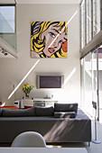 Pop-Art-Wandbild über Sitzbereich mit Sofa und Fernseher in Wohnraum mit hohen Wänden und Galerie