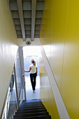 Narrow stairwell with yellow walls in modern architect-designed house