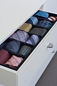 Various neckties in open drawer