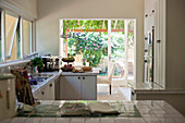 White-tiled worksurface in country-house kitchen with terrace access