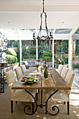 Wooden table and chairs with cream upholstery in country-house-style dining area