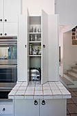 White kitchen cupboard with open doors over tiled worksurface in country-house kitchen