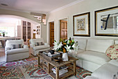 White corner sofa and armchairs around wooden coffee table in country-house-style living room