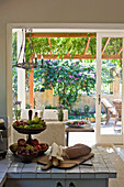 View from country-house kitchen onto summery roofed terrace through sliding doors