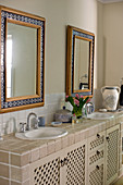 Mosaic-framed mirrors above tiled washstand in country-house-style bathroom