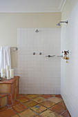White-tiled open shower area in bathroom with terracotta floor tiles