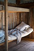 Simple sleeping area in rustic wooden cabin