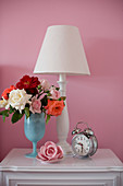 Vase of roses, table lamp and old-fashioned alarm clock on bedside cabinet against pink wall