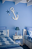 Bedside table between twin beds in blue-and-white maritime bedroom