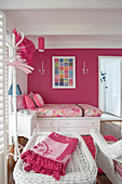 Single bed and rattan furniture in pink-and-white feminine bedroom