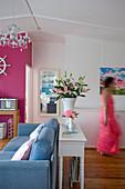 Konsolentisch hinter blauem Sofa in Wohnraum mit pinkfarbenen und weißen Wänden