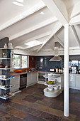 Stone floor tiles and white wood-beamed ceiling in open-plan kitchen in modern country-house style