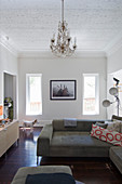 Retro furniture and chandelier in small, eclectic living room