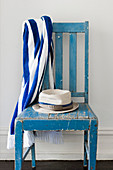 Hat and striped towel on blue, vintage wooden chair