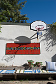Basketball basket, mosaic artwork on wall and low wooden seating in original courtyard