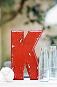 Red, vintage letter K next to seashell and glass bottles