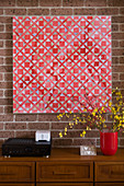Red geometric artwork on brick wall above wooden chest of drawers