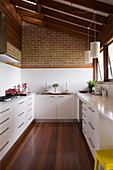 U-shaped kitchen with white cabinets and dark wooden floor below sloping wooden ceiling