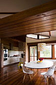 Open-plan kitchen and dining area below suspended wooden ceiling