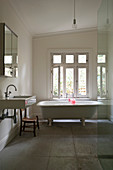 White bathroom in simple country-house style with free-standing bathtub and stone floor tiles