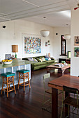 Sofa, stools and breakfast bar and dining table in vintage-style, open-plan interior