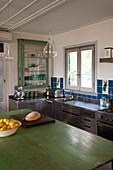 Edelstahlküche im Vintagestil mit moosgrüner Holzplatte auf Kücheninsel